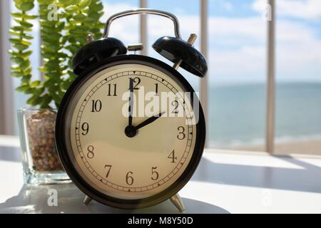 Daylight Savings Spring Forward sunday at 2:00 a.m. March 25. Plant, seascape and Sunlight in the background - Stock Photo
