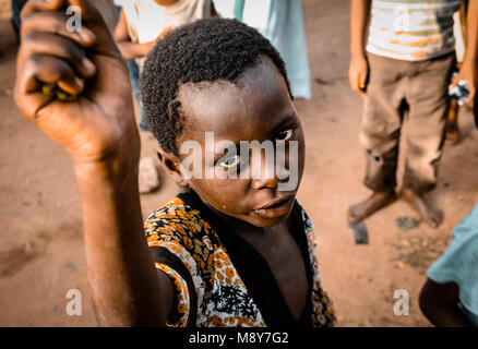 An African-colored child asks for help as he is portrayed intently staring at the camera lens, in a village near - Stock Photo