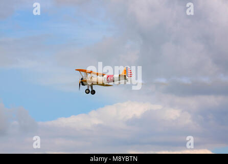 The Boeing Stearman N2S-3 in US Navy markings flying over cloudy sky during International Air Show at the 90th Jubilee - Stock Photo