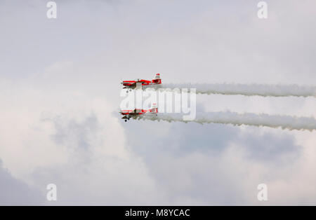 Pair of a Zlin Z-50LS of the Zelazny Aerobatic Team flying over sky during International Air Show at the 90th Jubilee - Stock Photo