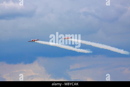 Pair of a Zlin Z-50LS of the Zelazny Aerobatic Team flying over stormy clouds during International Air Show. Deblin, - Stock Photo