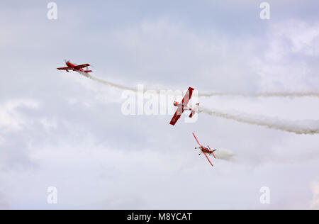 The Extra 330 LC and two of a Zlin Z-50LS of the Zelazny Aerobatic Team flying over cloudy sky during International - Stock Photo