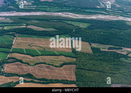 Aerial view of green fields with crops and other plows awaiting planting. Also with virgin mountain and river - Stock Photo
