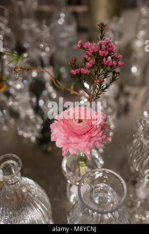Table decorated with pink rosemary flower and carnation in glass crystal vases - Stock Photo