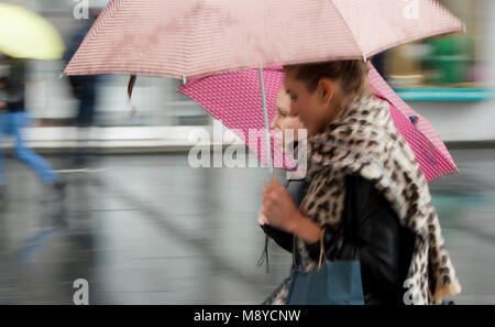 Belgrade, Serbia - September 25, 2017: Blurry panning shot of two pretty girls talking while walking together under - Stock Photo