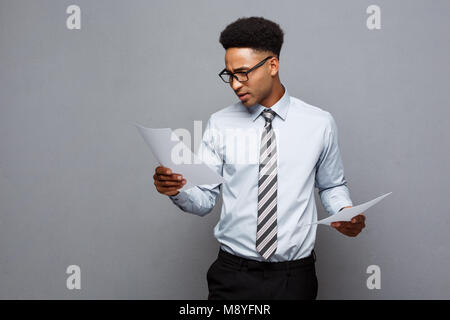 Business Concept - handsome young professional african american businessman concentrated reading on document paper. - Stock Photo