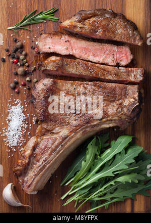 Grilled cowboy beef steak, herbs and spices on a wooden board. Top view - Stock Photo
