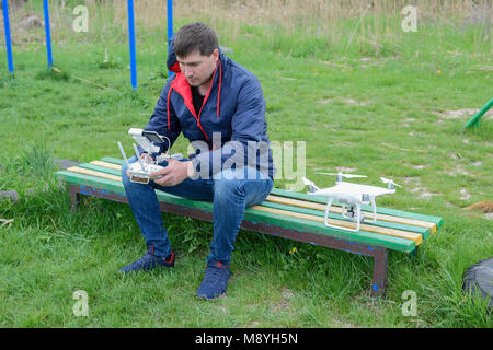 A man with a remote control drone in his hands is sitting - Stock Photo