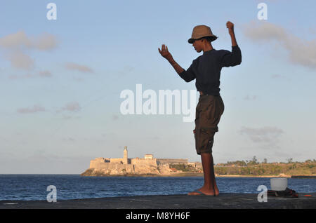 A boy fishes by hand from the seawall of the Malecon in Havana, Cuba, with the fortress known as Morro Castle (El - Stock Photo