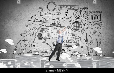 Businessman playing fife while standing on pile of documents among flying paper planes with eco-analytical information - Stock Photo