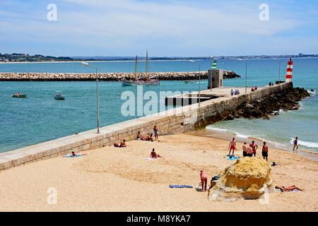 Tourists relaxing on Praia da Batata beach with holidaymakers on boats to the rear, Lagos, Algarve, Portugal, Europe. - Stock Photo