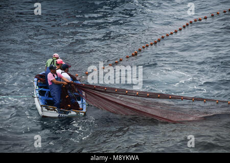 Fisherman in a small boat hauling in their net - Stock Photo