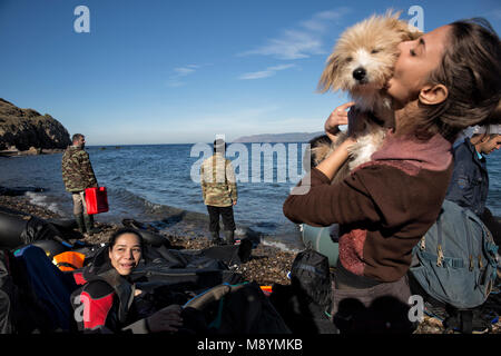 A Syrian girl from Aleppo kisses her dog after she and her family arrived after crossing the Aegean Sea, seeking - Stock Photo