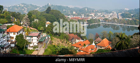 A 2 picture stitch panoramic cityscape aerial view of Kandy in Sri Lanka with Kandy Lake on a sunny day with blue - Stock Photo