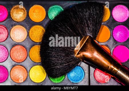 professional brush on multi-colored, beautiful shadows for eyes, background image - Stock Photo