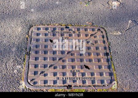 Stanton and Staveley manhole cover on a pavement, Dorset, United Kingdom - Stock Photo