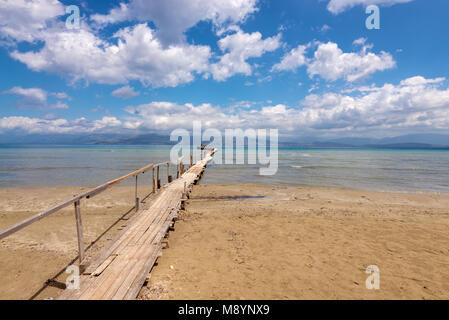 Wooden pier on Apraos beach near Kassiopi town with perfect views of the Albanian mountains. Corfu island. Greece. - Stock Photo