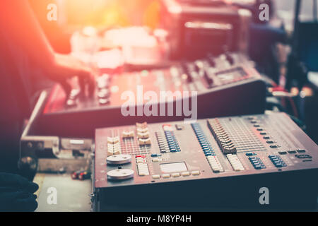 professional stage sound mixer closeup at sound engineer hand using audio mix slider working during concert perfomance - Stock Photo