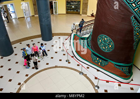 Visitors standing next to the world's largest shoes, a giant traditional Mongol boot in the Chinggis Khaan Statue - Stock Photo
