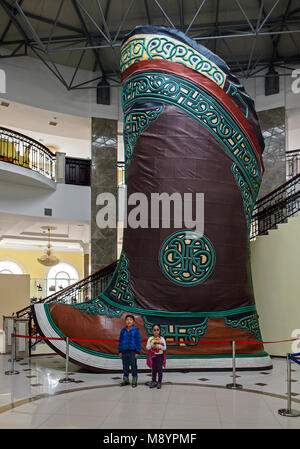 Kids standing next to the world's largest shoes, a giant traditional Mongol boot in the Chinggis Khaan Statue Complex, - Stock Photo