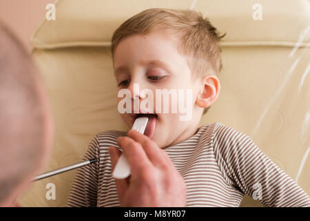 Little boy in clinic show tongue for pediatrician. Doctor examining patients mouth with spatula. - Stock Photo