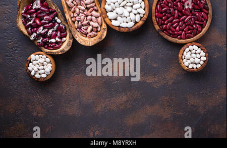 Different type of beans in wooden bowls  - Stock Photo
