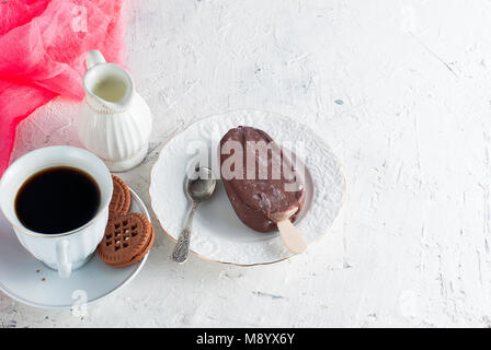 Breakfast tasty ice cream in milk chocolate and a cup of strong black coffee - Stock Photo