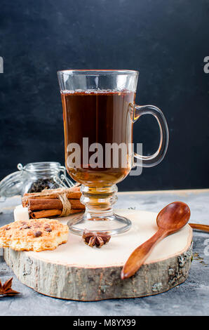 Black tea in cup on dark  background, Cup of tea, biscuits, spices for tea. - Stock Photo