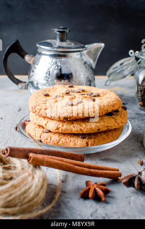 stack of homemade cookies with chocolate drops, сup of hot black tea, cinnamon, anise on dark   background, spices - Stock Photo