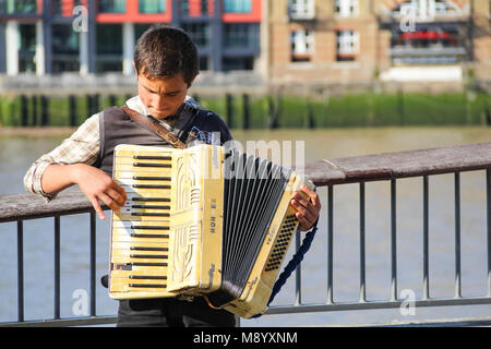 London, UK - July 09, 2017 - A young busker performing accordion on a riverside street at South Bank - Stock Photo