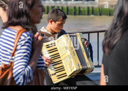 London, UK - July 09, 2017 - A young busker performing accordion on a crowd street at South Bank - Stock Photo