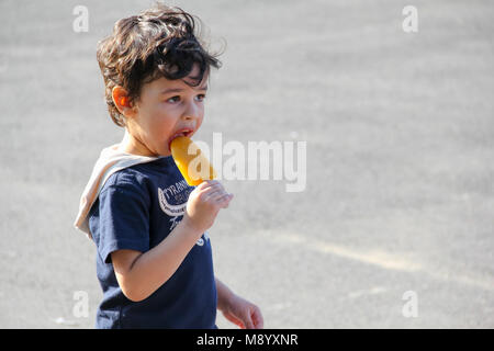 London, UK - July 09, 2017 - Little boy eating ice lolly at South Bank in hot weather - Stock Photo