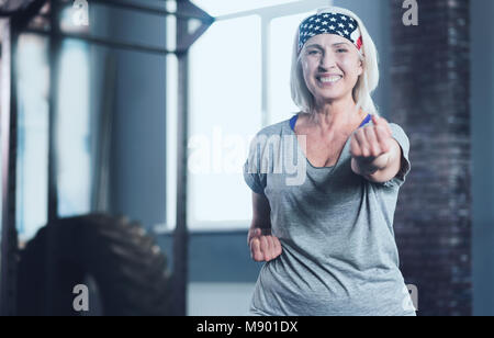 Radiant woman looking into camera while taking exercise class - Stock Photo