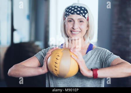 Elderly lady holding ball while training at gym - Stock Photo