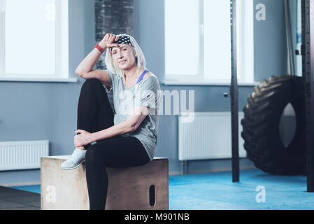 Sporty retired woman relaxing on wooden box at gym - Stock Photo