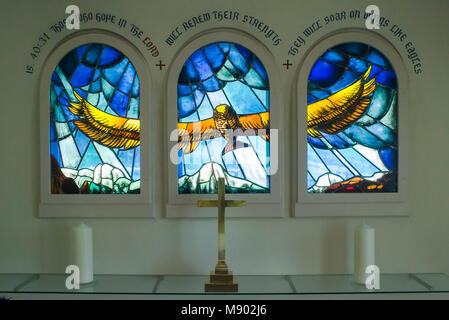 Impressive thriple stained glass window featuring a flying eagle with outstretched wings above the Bernese Oberland - Stock Photo