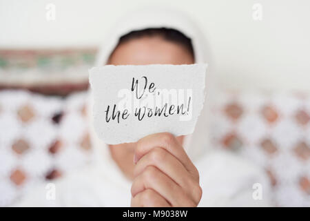 closeup of a young woman indoors wearing a white hijab showing a piece of paper in front of her face with the text - Stock Photo