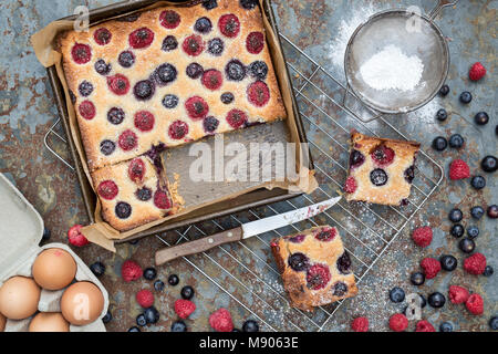 Homemade raspberry and blueberry frangipane tart with ingredients on a slate background - Stock Photo
