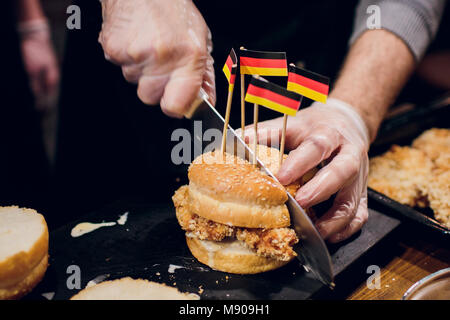 Chief cook preparing fresh burger in the kitchen.Burger restaurant menu cooking process. The cook cuts a bun on - Stock Photo