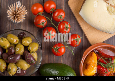 Mixed spanish tapas starters on table. Manchego cheese, olives and grilled pepper. Top view - Stock Photo