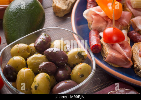 Sharing mixed spanish tapas starters on table. Olives, sandwiches and avocado. - Stock Photo
