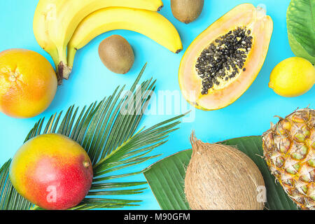 Ripe Juicy Mango Halved Papaya Coconut Kiwi Bananas on Large Palm Leaf on Light Blue Background. Summer Vacation - Stock Photo