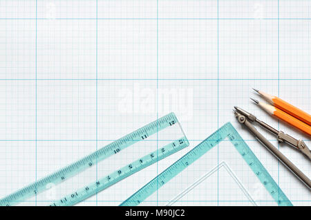 Divider, pencils and rulers on blue graph paper background - Stock Photo