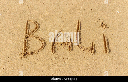 The inscription on the sand of Bali. Vacation time, beach holidays. - Stock Photo