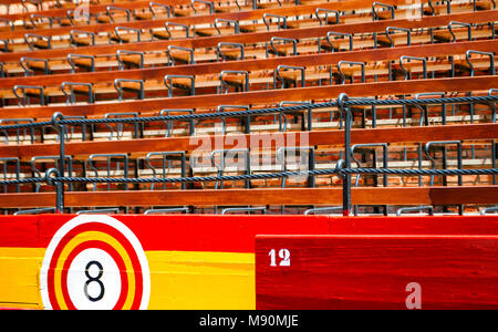detail of the seats inside an ancient Spanish arena with wooden seats and barriers with the colors of the Spanish flag - Stock Photo