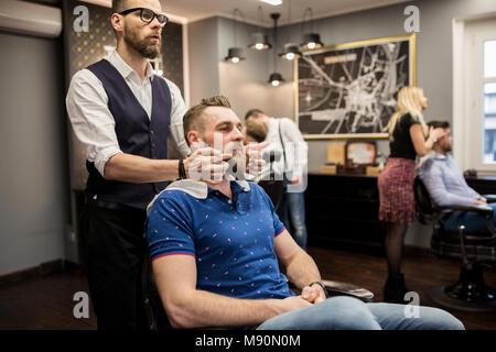 Portrait of barber preparing customer for shaving - Stock Photo