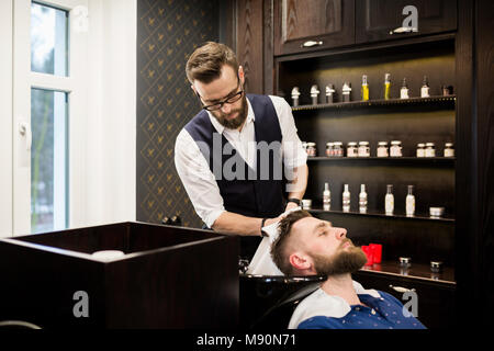 Portrait of young barber wiping customer hair with towel - Stock Photo