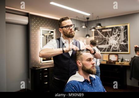 Portrait of hairdresser combing customer hair - Stock Photo