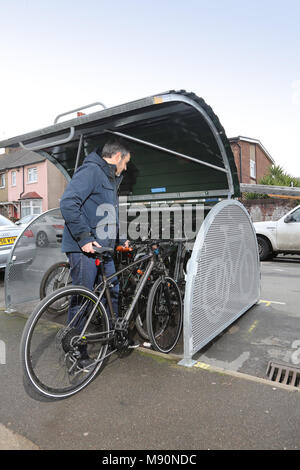 A cyclist places his bike into a secure on-street bicycle store recently installed on a residential London street. - Stock Photo