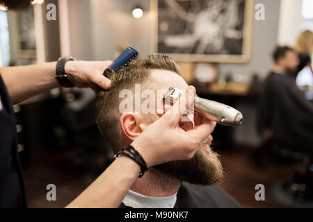 Portrait of bearded man being shaved at barber shop - Stock Photo